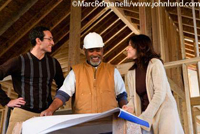 Picture of a couple meeting with thier general contractor at their new home being built. The couple look very happy and are looking at each other.